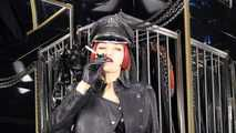 Mistress Tokyo smoking cigarette in leather, gloves and Muir Cap; fetish, POV